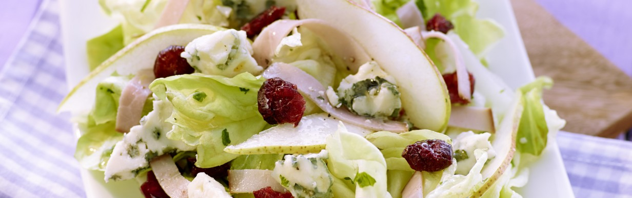 Kopfsalat mit feinen Kräutern, Birne, Roquefort, Schinkenstreifen und Cranberries