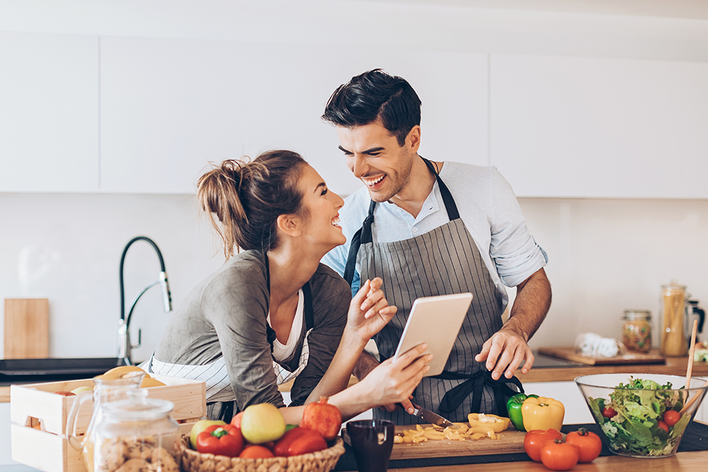 Lovely couple with digital tablet and fresh vegetables in the kitchen.